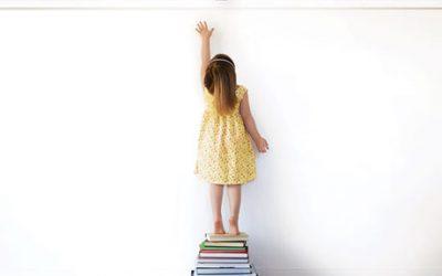 girl standing on books