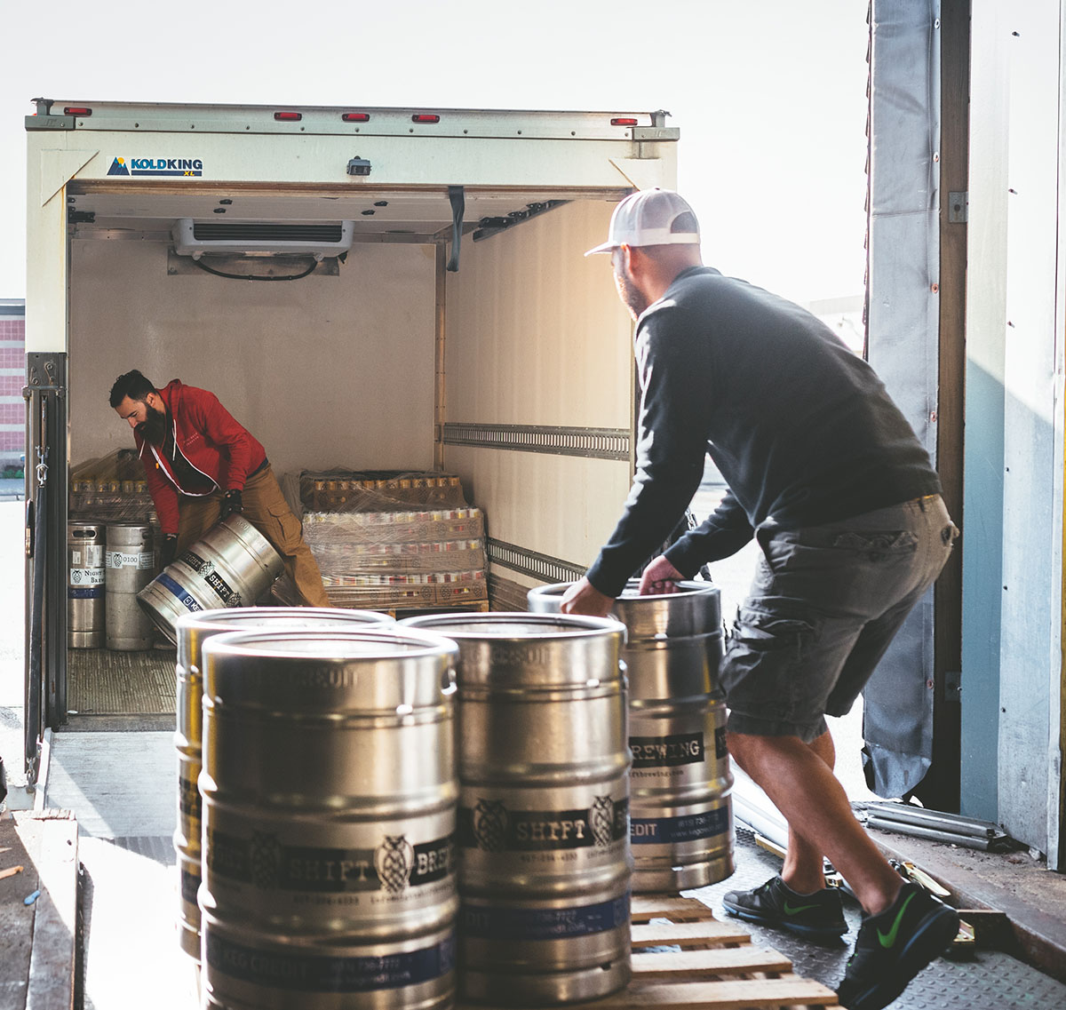 Night Shift warehouse assistant Marlon Silvestre (L) and delivery driver Justin Dirienzo loading kegs into a refrigerated box truck