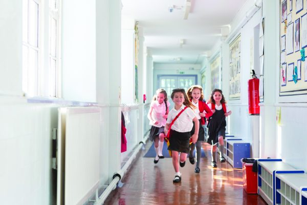 Small group of schoolgirls running down the corridor of a school. The girls look ecstatic with smiles on their faces. They are wearing school uniform carrying their schoolbags.