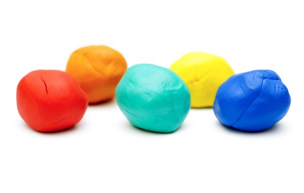 Five pieces of colored plasticine on white background.