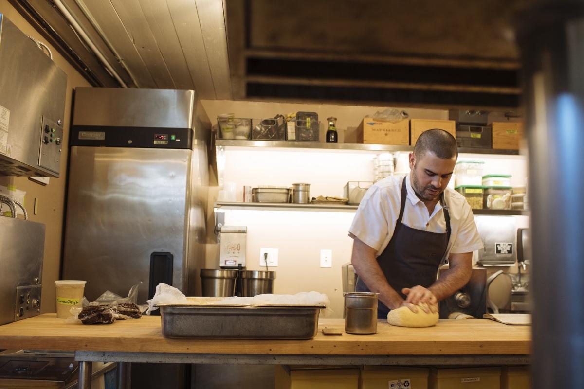 Chef Brendan Joy kneads pizza dough at Steel & Rye