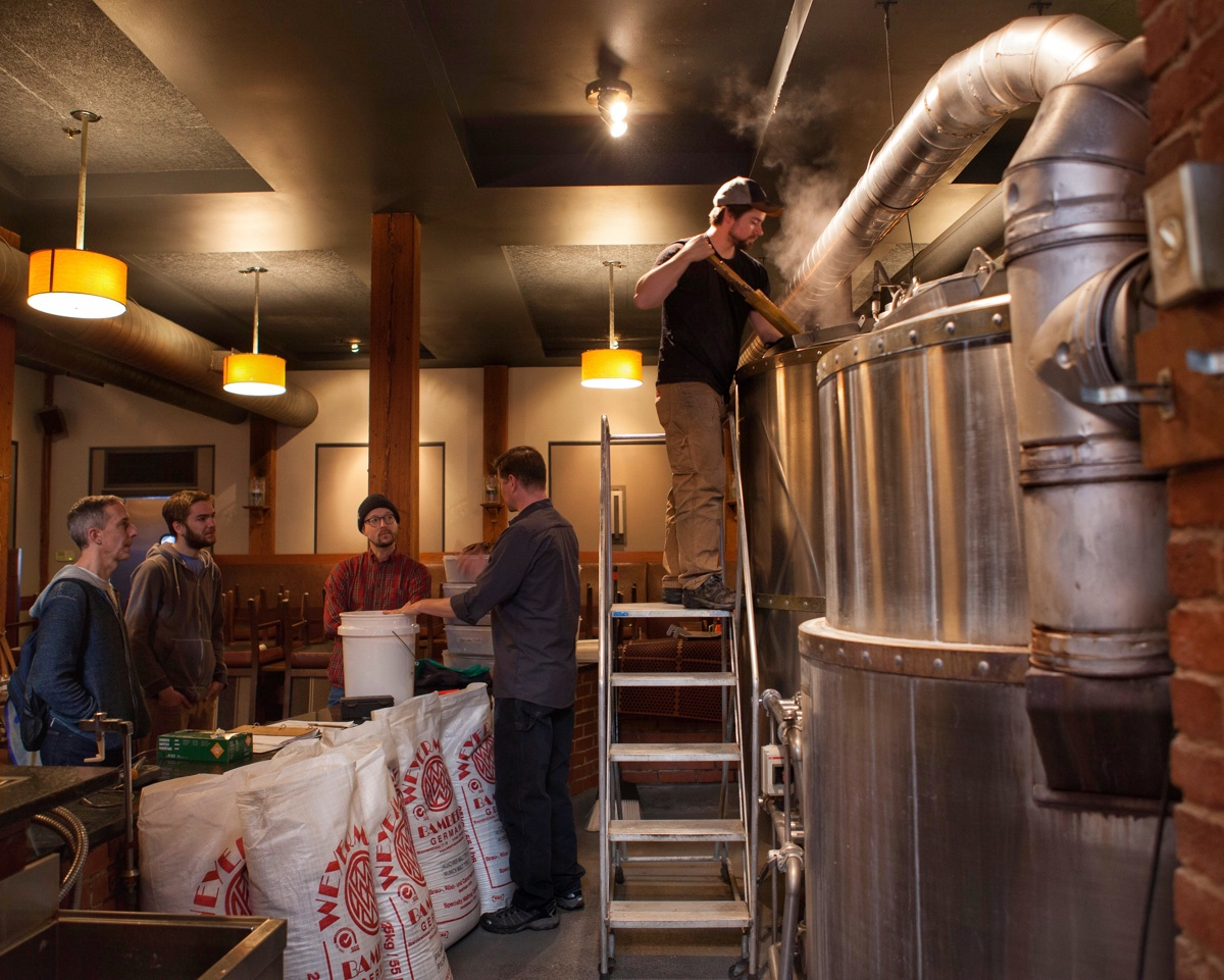 Mamaleh's employees discuss a collaboration bagel beer with brewmaster Will Meyers while assistant brewer Kevin Dwyer stirs the mash