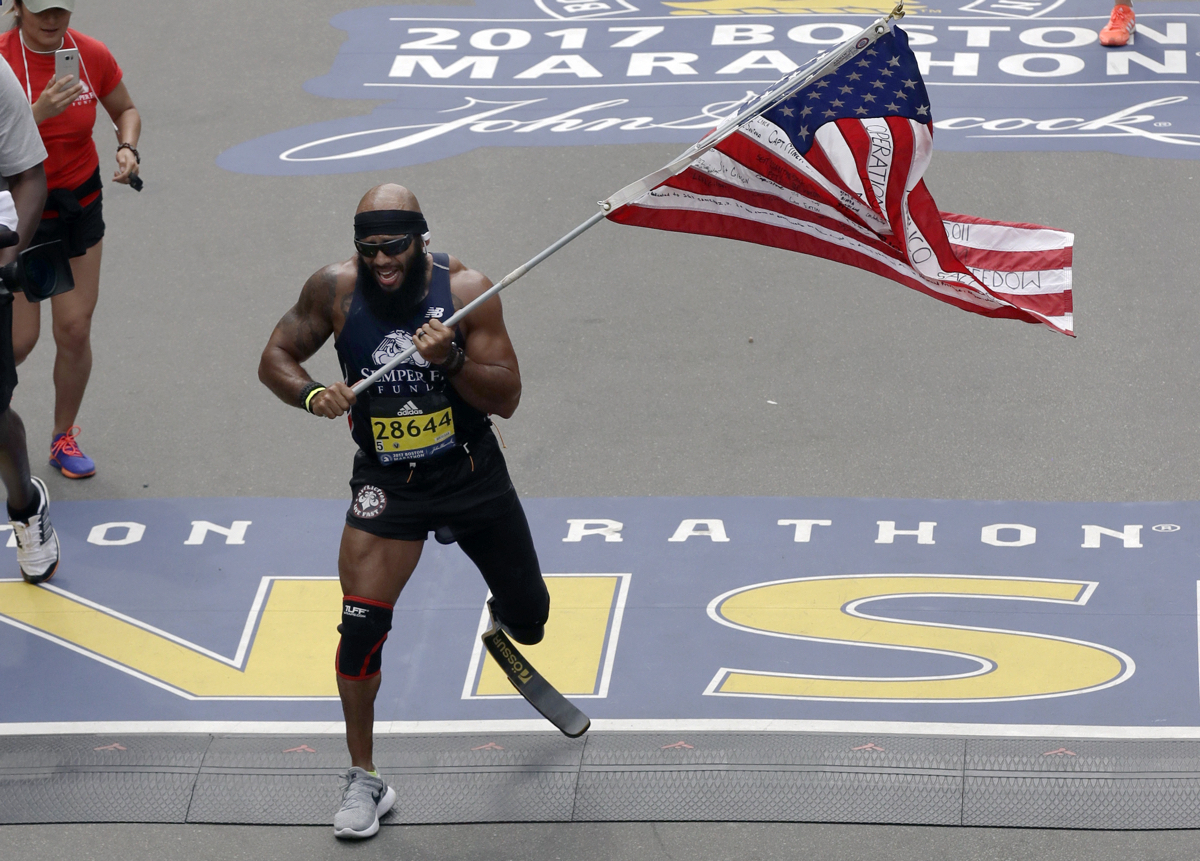Jose Sanchez, of San Antonio, carries the United States flag across the finish line in the 121st Boston Marathon on Monday, April 17, 2017, in Boston. (AP Photo/Charles Krupa)