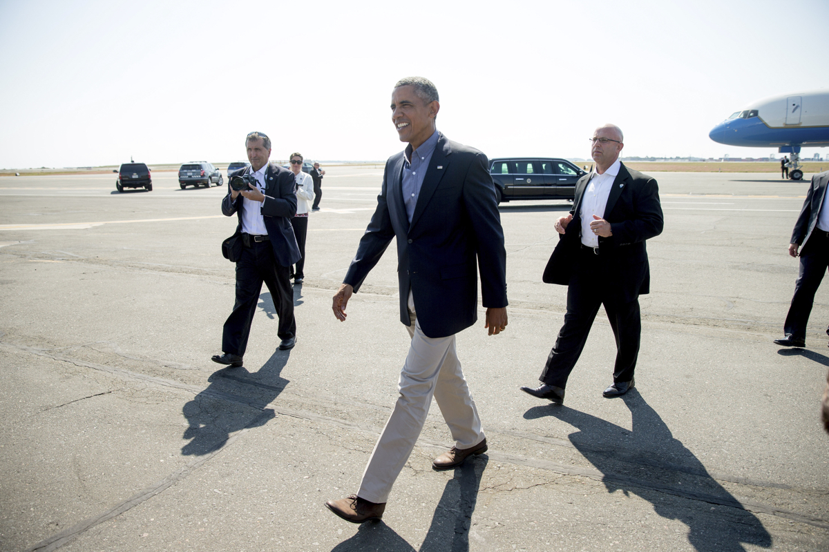 President Barack Obama walks across the tarmac to greet visitors as he arrives at Boston Logan International Airport in Boson, Monday, Sept. 7, 2015, to speak at the Greater Boston Labor Council Labor Day Breakfast. Obama will sign an Executive Order requiring federal contractors to offer their employees up to seven days of paid sick leave per year. (AP Photo/Andrew Harnik)