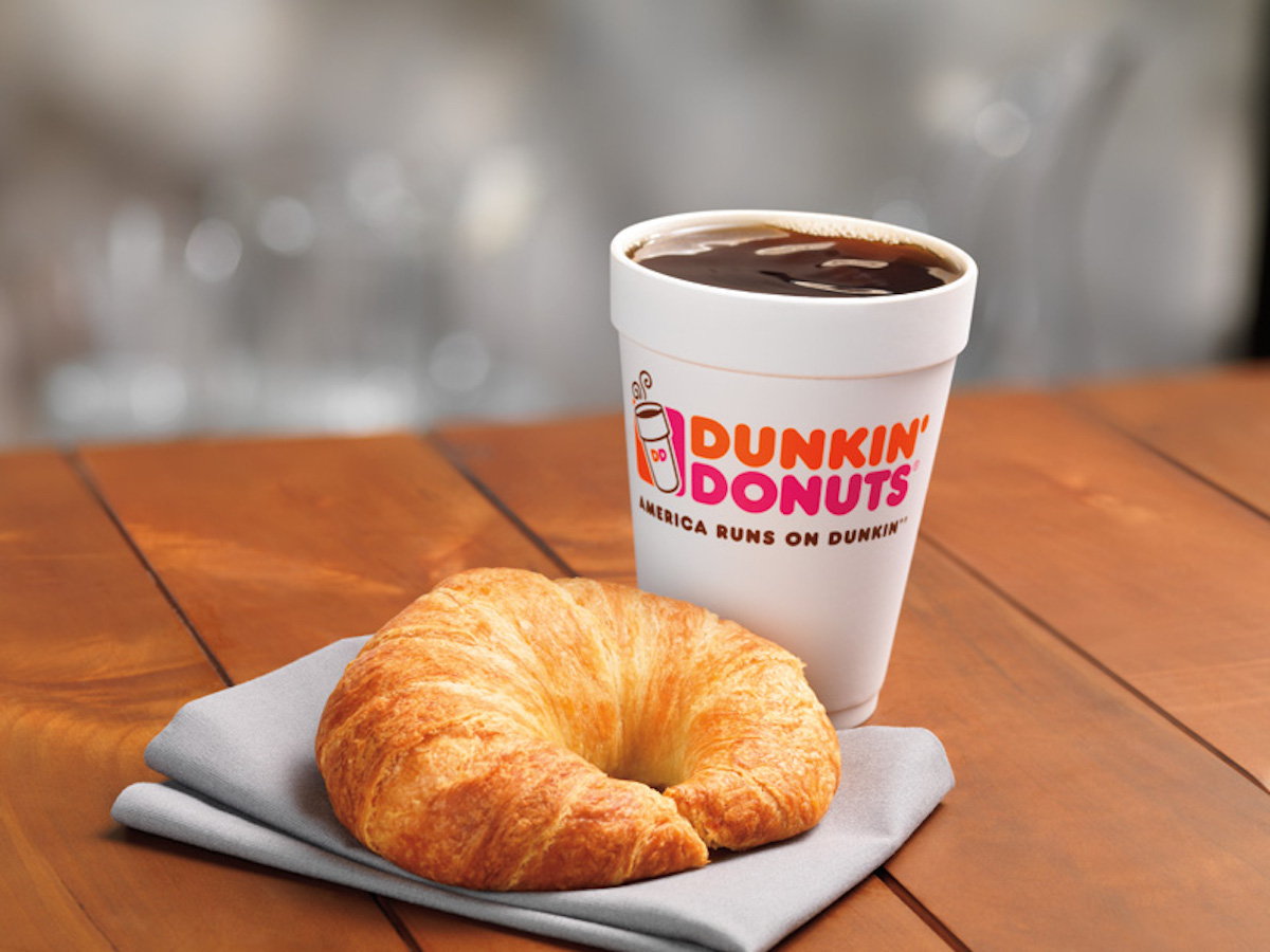A hot Dunkin' Donuts coffee with a croissant