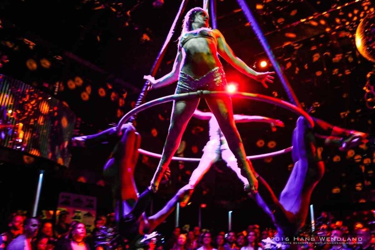 An acrobat dressed as a zombie suspends herself on a ring