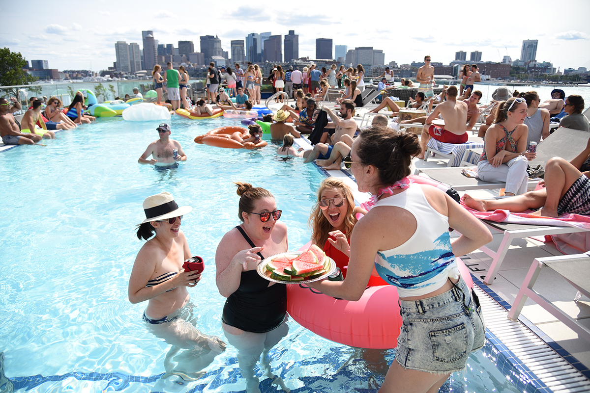East Boston Oysters creative coordinator Grace Ghazey serves guests watermelon off a sliver platter at an EBO Pool Party in 2017