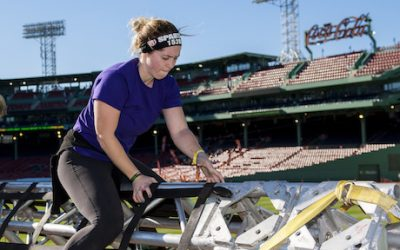 A woman climbs over a structure at Fenway Park
