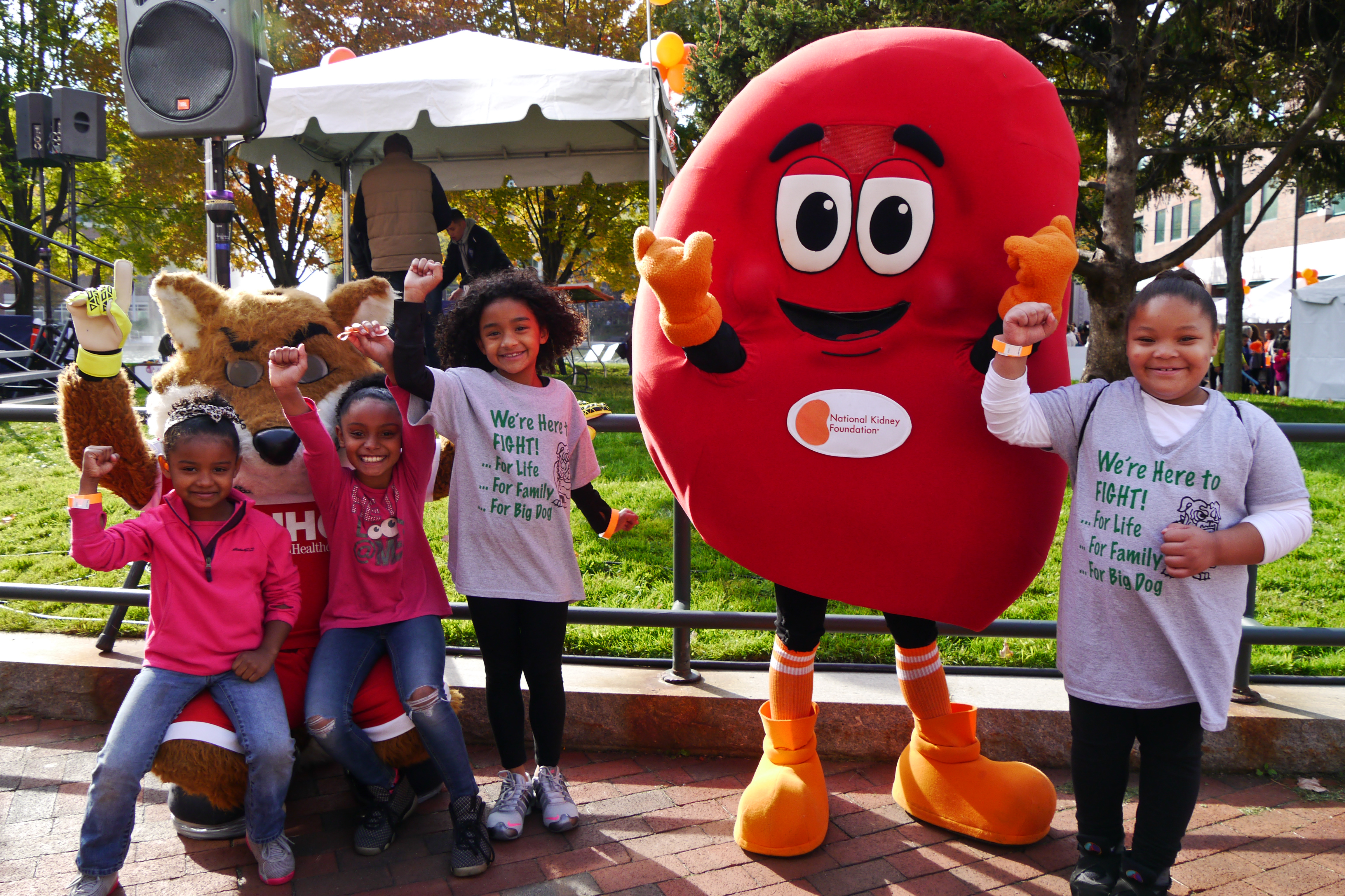 Children standing next to someone in a kidney costume