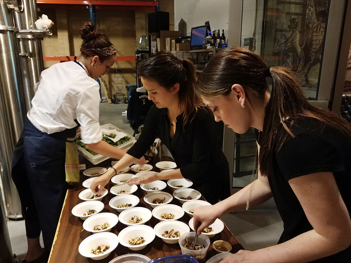 Chef Rachel Miller, Liana Van de Water, sommelier Kelsey McCallan plater during a Nightshade pop-up at Deacon Giles Distillery in Salem