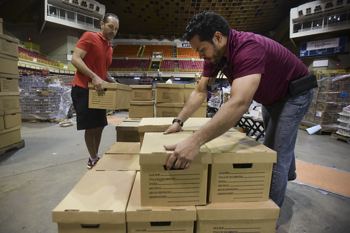 Men move cardboard boxes in a large arena