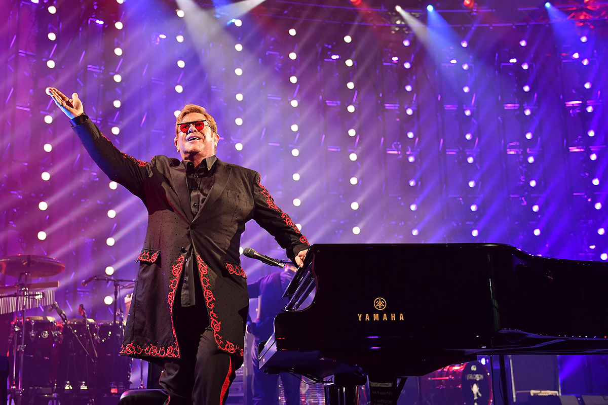 Elton John stands next to a piano in front of a purple background