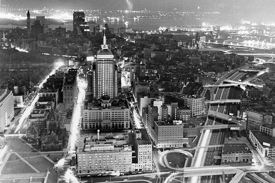 A black and white photo of Boston, mostly encased in darkness with a few pockets of bright light.