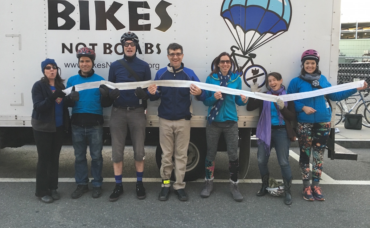 A group of cyclists hold a grocery store receipt