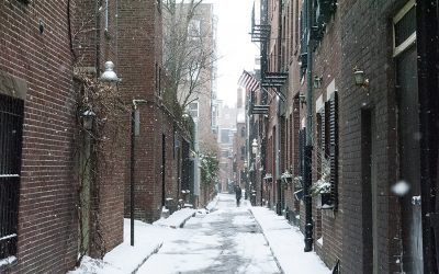 A snowy street lined with brick buildings