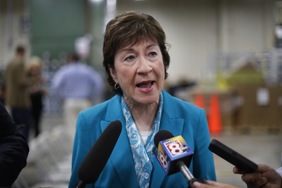 Susan Collins speaks into two microphones