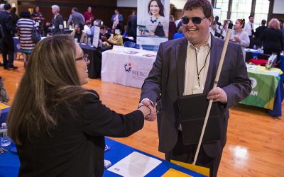 A man wearing sunglasses and holding a white cane shakes hands with a job recruiter