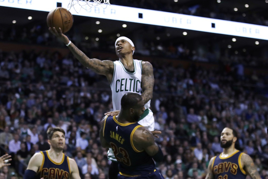 The Celtics' Isaiah Thomas jumps over the Cavaliers' LeBron James toward the hoop