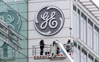 Workers stand on a crane in front of the GE logo