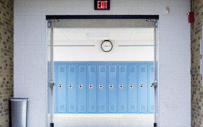 Blue lockers beneath a clock and an exit sign