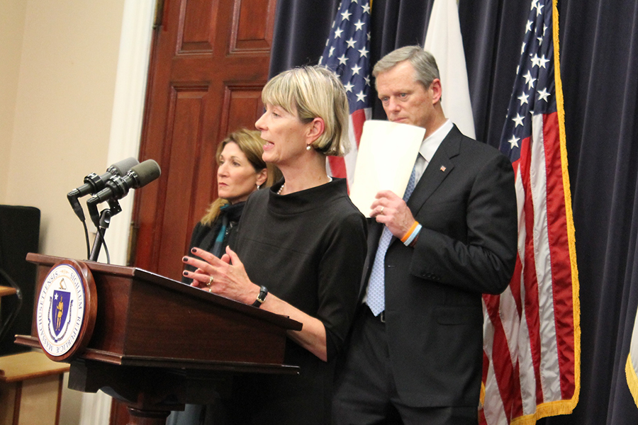Marylou Sudders speaks at a lectern with Charlie Baker behind her
