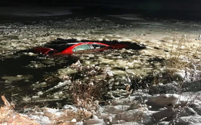 A red car sinking into an icy pond