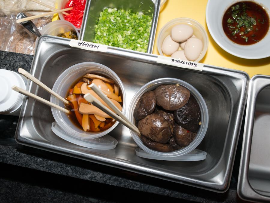 Marinated mushrooms and more ingredients ready for ramen bowls at Oisa Ramen Slurp & Go