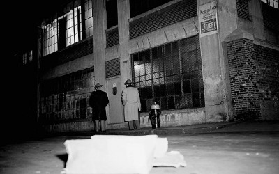 "Two unidentified people look at entrance of Brink's Inc., an armored truck firm's garage on Prince Street, in Boston, Massachusetts, Jan. 17, 1950, where seven gunmen tied up five employees and robbed an open vault of ""more than $500,000 in cash."" Police, reconstructing the holdup, said the robbers reached the vault on the second floor of the garage by opening six locked door, ""probably with a passkey."""