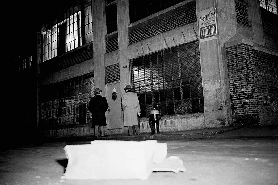 """Two unidentified people look at entrance of Brink's Inc., an armored truck firm's garage on Prince Street, in Boston, Massachusetts, Jan. 17, 1950, where seven gunmen tied up five employees and robbed an open vault of """"more than $500,000 in cash."""" Police, reconstructing the holdup, said the robbers reached the vault on the second floor of the garage by opening six locked door, """"probably with a passkey."""""""