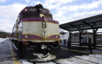 A commuter rail train pulls into a station