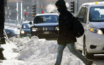 A man walks bundled up through a snowy intersection