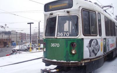 A green line train travels through a snowy terrain