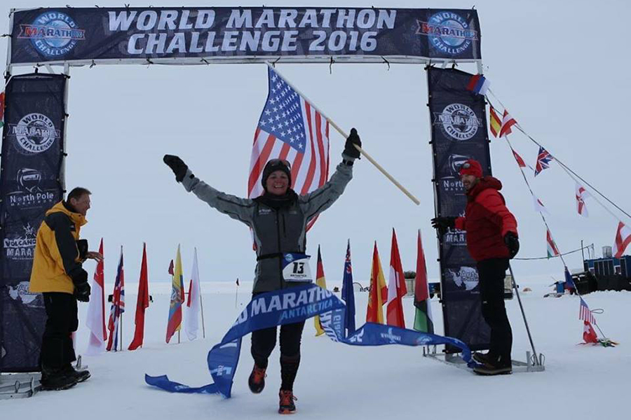 A woman crosses the finish line of a marathon wearing a lot of cold gear