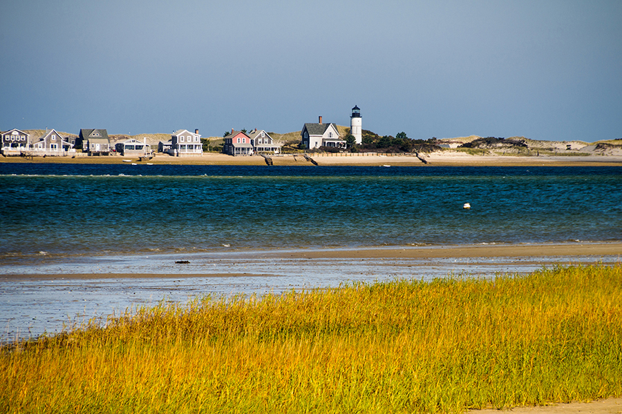 The cottages and lighthouse at the tip of Sandy Neck as seen from across Barnstable Harbor beach.