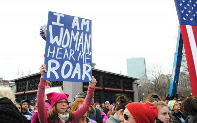 "A woman holding a poster that says ""I am woman, hear me roar"""