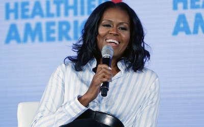 Michelle Obama smiles while holding a microphone
