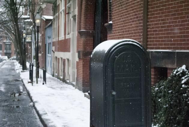 A snow-covered mailbox and brick building in Beacon Hill