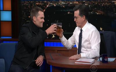 Tom Brady and Stephen Colbert clink beers