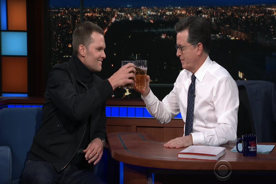 Tom Brady and Stephen Colbert clink beers