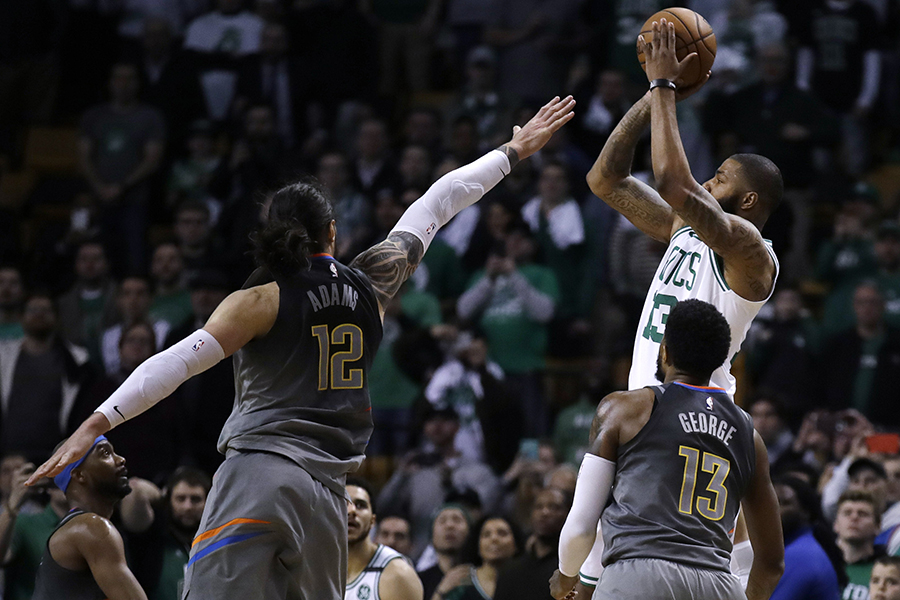 Boston Celtics forward Marcus Morris, top right, puts up his game-winning 3-point shot over Oklahoma City Thunder center Steven Adams (12) and forward Paul George in an NBA basketball game in Boston, Tuesday, March 20, 2018. The Celtics won 100-99. (