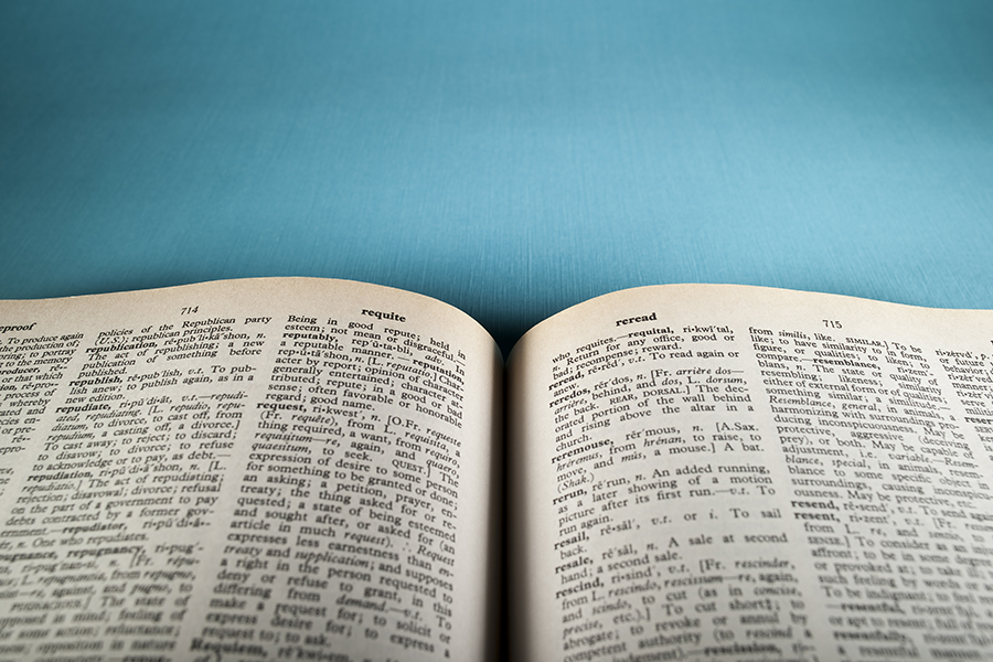 An open dictionary against a blue backdrop