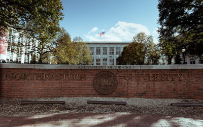 A brick wall with the Northeastern University name and crest