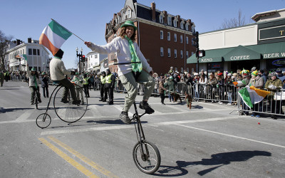 A member of the Cycling Murrays holds an Irish flag while riding a unicycle during the annual St. Patrick's Day parade, Sunday, March 18, 2018, in Boston. The city's 117th St. Patrick's Day Parade followed a shortened snow route used three of the past four years due to the buildup of snow from three recent nor'easters.