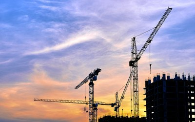 Construction site at dusk evening yellow back light, blue cloudy sky, silhouette cranes, sunlight