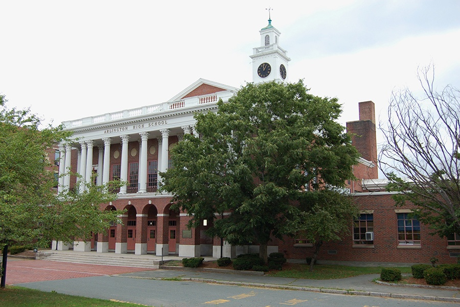 A stately brick building with a clock tower and columns
