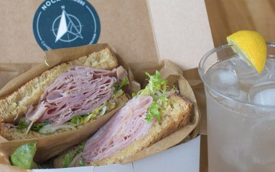 Noca Provisions' ham and Swiss sandwich with frisée and apple mostarda, and a house-made lemon lavender soda packed up for a picnic