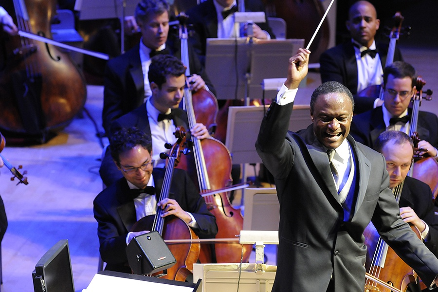 Thomas Wilkins holds his baton and conducts the orchestra while smiling