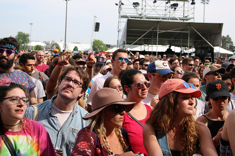 A sun-drenched crowd looks up at the stage