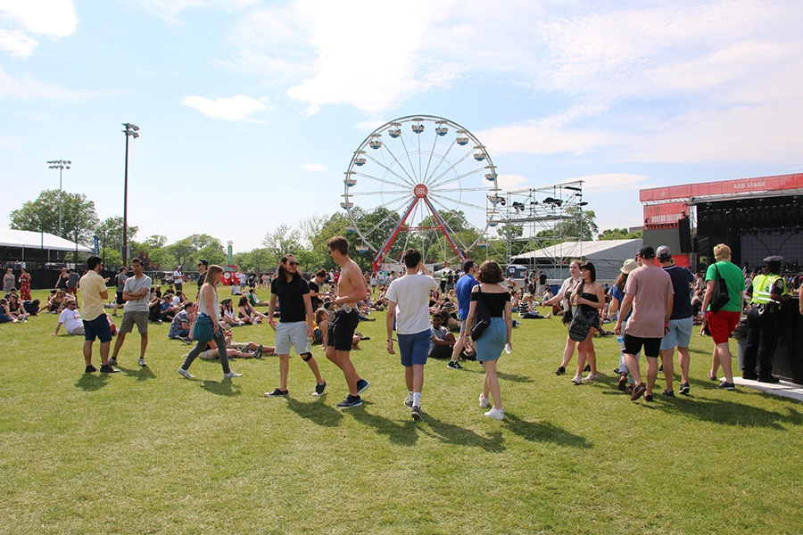 Fans walk in front of a ferris wheel at Boston Calling