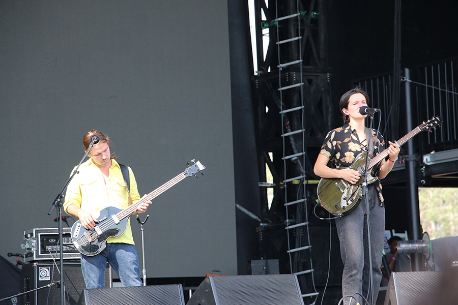 A pair of musicians with guitars play on stage